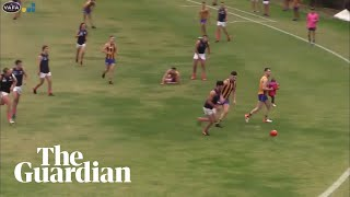 Toddler rescued by Aussie Rules player after running on to pitch during match