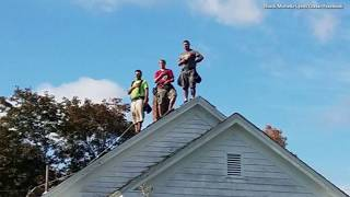 Roofers Pictured Standing For National Anthem during High School Football Game