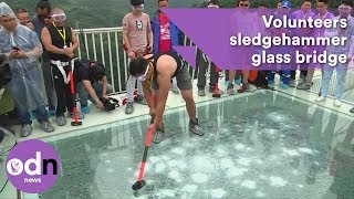 Volunteers sledgehammer glass bridge to test strength